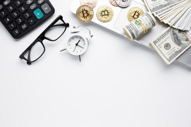 Vista superior de moedas e papel-moeda no laptop Foto gratuita