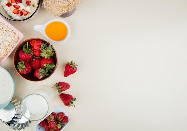 Vista superior de morangos em uma tigela com manteiga de queijo cottage leite aveia no lado esquerdo e superfície branca com espaço de cópia Foto gratuita