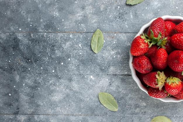 Vista superior de morangos vermelhos frescos dentro de um prato branco junto com folhas verdes secas em madeira cinza, vitamina de frutas frescas foto colorida saúde Foto gratuita