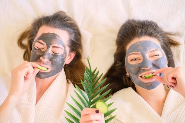 Vista superior de mulheres com máscaras de rosto comendo fatias de pepino Foto gratuita