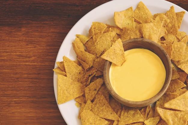 Vista superior de nachos com molho de queijo Foto Premium