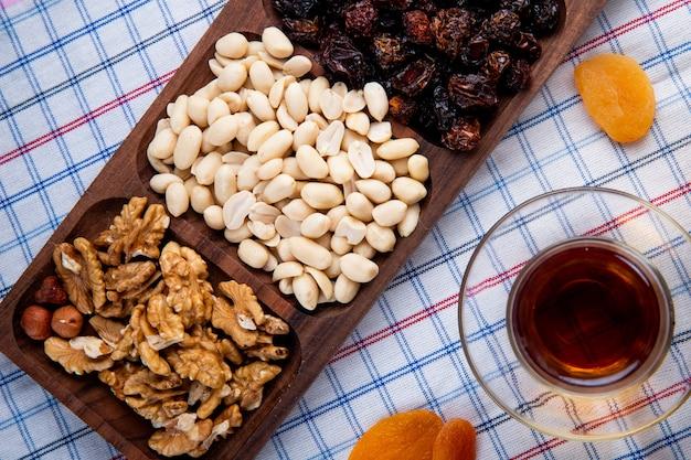 Vista superior de nozes mistas com frutas secas em uma caixa de madeira, servida com chá em copo armudu na toalha da mesa Foto gratuita