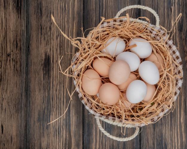 Vista superior de ovos de galinha fresca no ninho em um balde em um fundo de madeira com espaço de cópia Foto gratuita