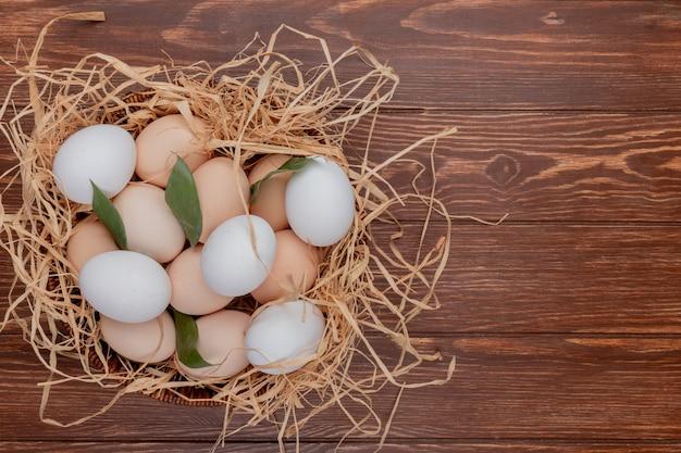 Vista superior de ovos de galinha no ninho com folhas em um fundo de madeira com espaço de cópia Foto gratuita