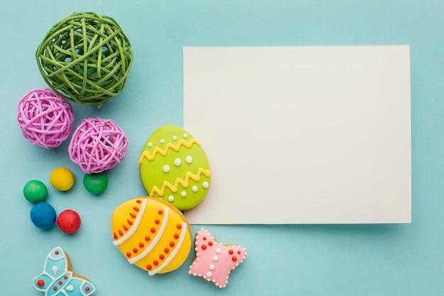 Vista superior de ovos de páscoa coloridos com borboleta e papel Foto gratuita