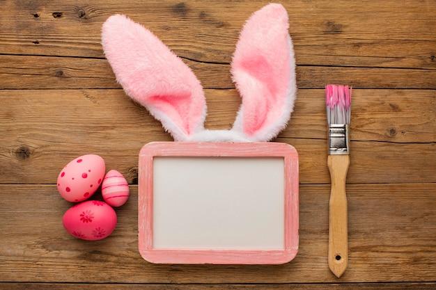 Vista superior de ovos de páscoa coloridos com moldura e pincel ao lado de orelhas de coelho Foto gratuita