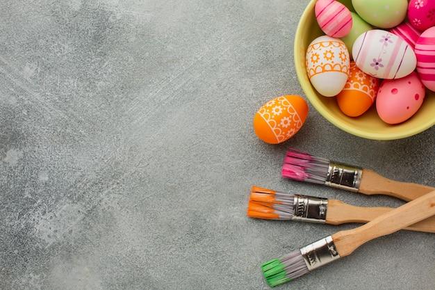 Vista superior de ovos de páscoa coloridos com pincéis e espaço de cópia Foto gratuita