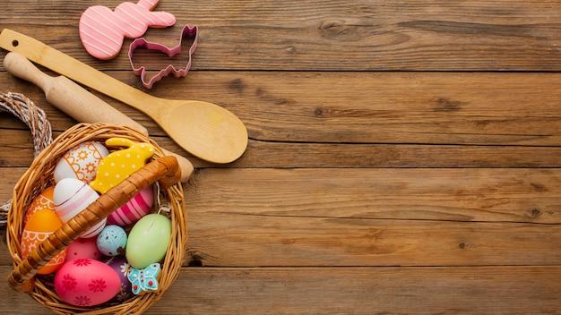 Vista superior de ovos de páscoa coloridos em uma cesta com utensílios de cozinha e espaço de cópia Foto gratuita