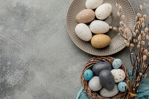 Vista superior de ovos de páscoa coloridos na cesta e prato com espaço de cópia Foto gratuita