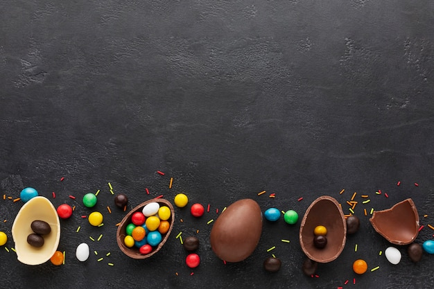 Vista superior de ovos de páscoa de chocolate cheios de doces coloridos Foto gratuita