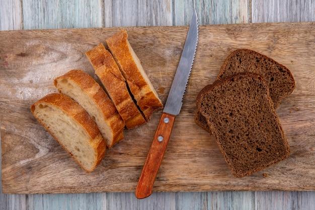 Vista superior de pães como baguetes fatiados e centeio com faca na tábua de corte no fundo de madeira Foto gratuita