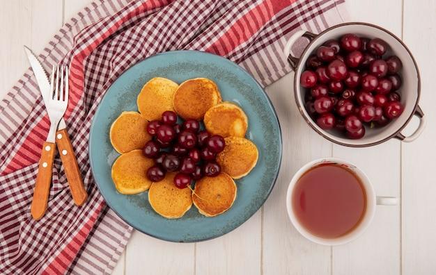 Vista superior de panquecas com cerejas no prato e garfo faca em pano xadrez e tigela de cerejas com uma xícara de chá no fundo de madeira Foto gratuita