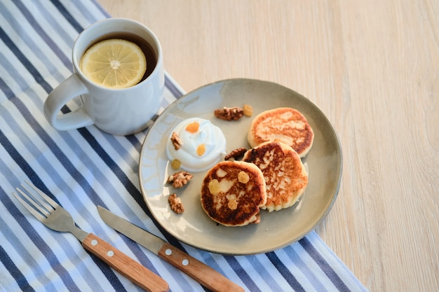 Vista superior de panquecas de queijo caseiro syrniki com creme de leite e xícara de chá Foto Premium