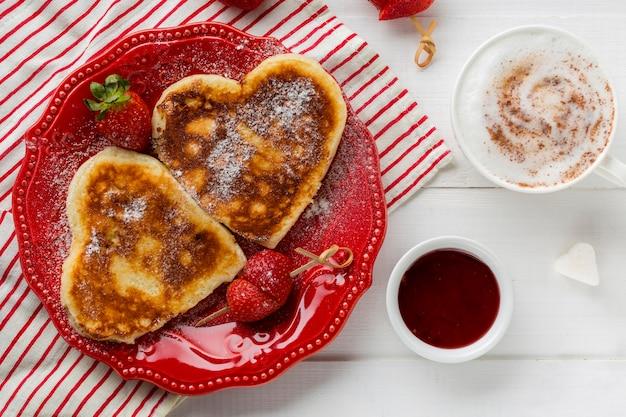 Vista superior de panquecas em forma de coração com morango Foto gratuita
