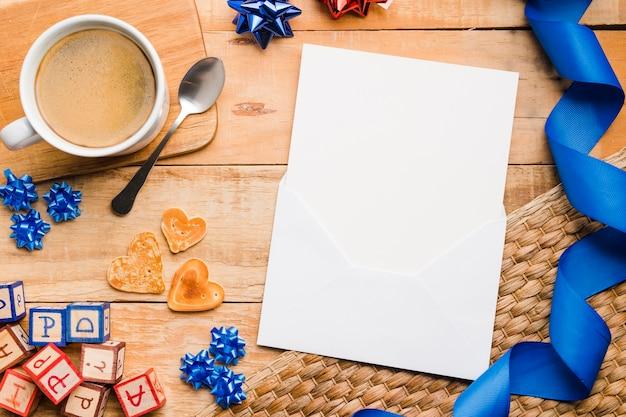 Vista superior de papel em branco com uma xícara de café na mesa Foto gratuita