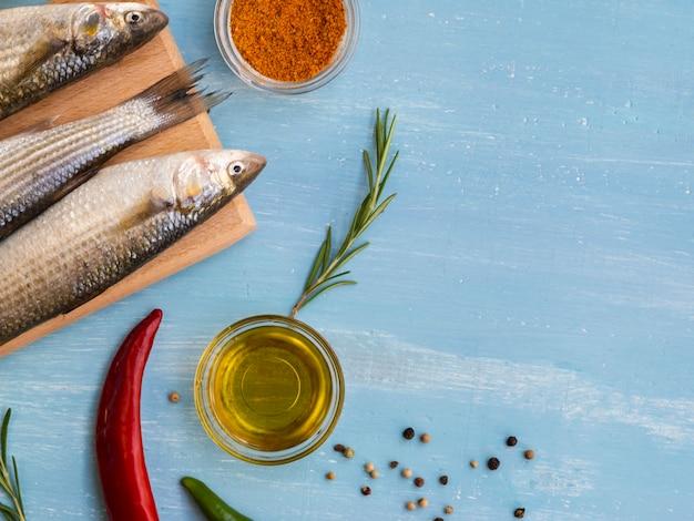 Vista superior de peixe fresco com condimentos Foto gratuita