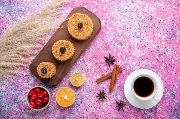 Vista superior de pequenos bolos deliciosos com canela e xícara de chá na superfície rosa claro Foto gratuita