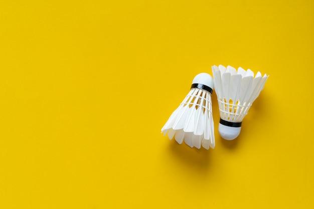 Vista superior de petecas brancas sobre fundo amarelo Foto Premium