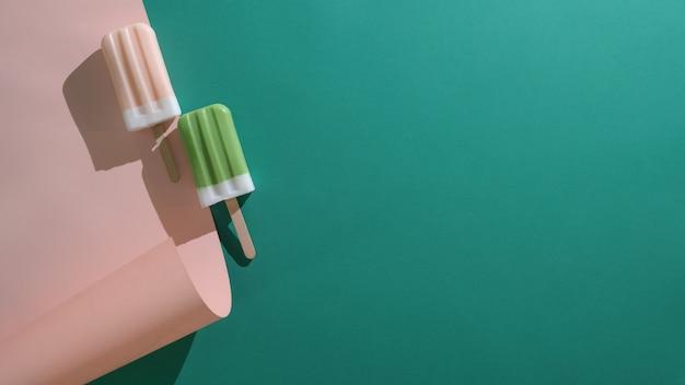 Vista superior de picolés de sabor de chá verde e morango e espaço da cópia no plano deite o fundo verde e rosa Foto Premium