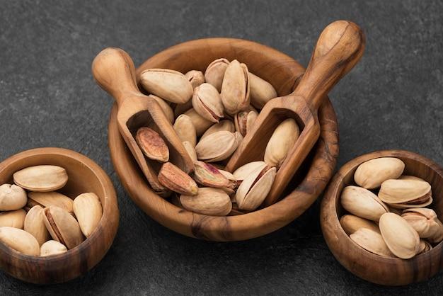 Vista superior de pistache em tigelas com colheres de madeira Foto gratuita
