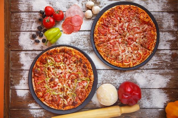 Vista superior de pizzas italianas com molho de tomate, queijo e pimentão Foto gratuita