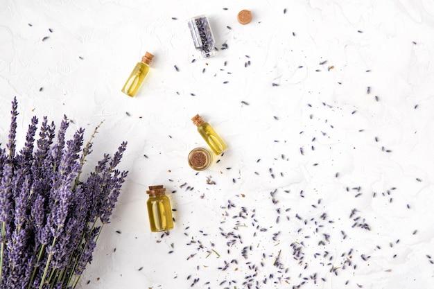 Vista superior de produtos de cuidados do corpo de óleo de lavanda com luz solar. aromaterapia, spa e conceito de saúde natural, plana leigos Foto Premium