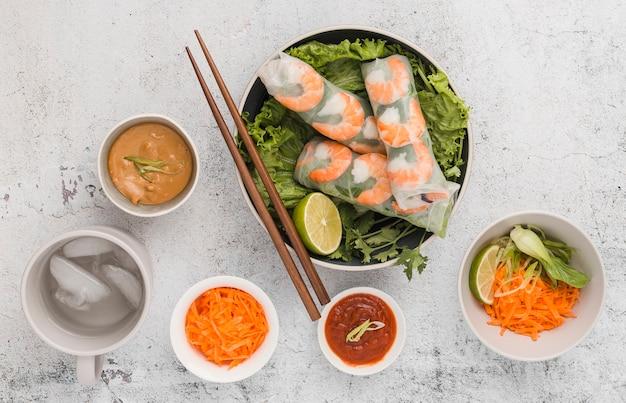 Vista superior de rolos de camarão fresco com salada e molho Foto gratuita
