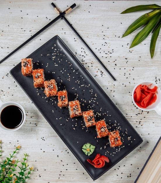 Vista superior de rolos de sushi com tobiko vermelho e gergelim Foto gratuita