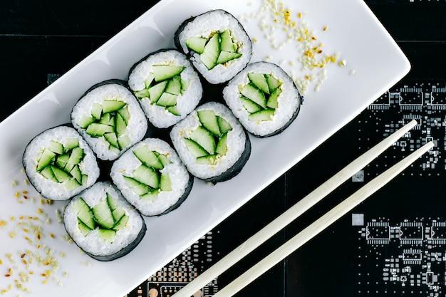 Vista superior de rolos de sushi nori com pepino Foto gratuita