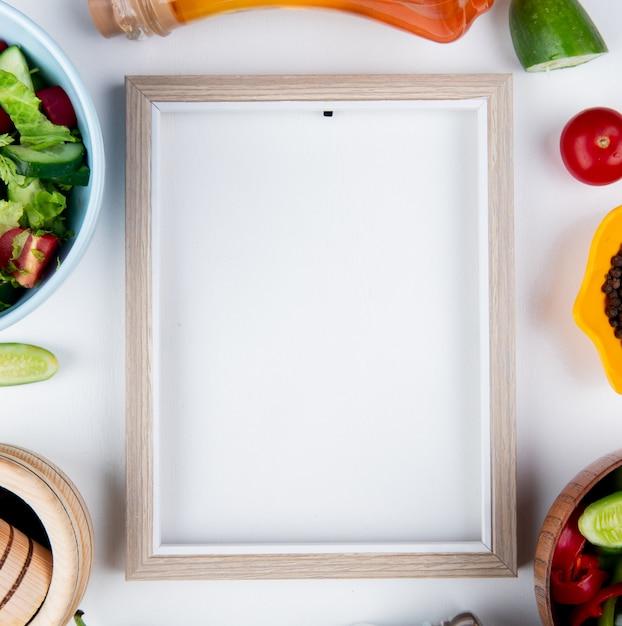 Vista superior de saladas de legumes e legumes como tomate pepino com pimenta preta derretida manteiga e moldura na superfície branca com espaço de cópia Foto gratuita