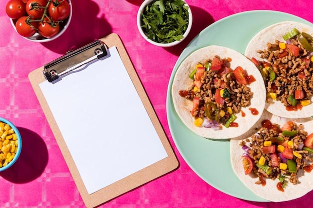 Vista superior de tacos e arranjo de prancheta Foto Premium