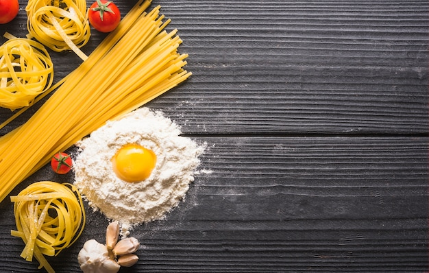 Vista superior, de, tagliatelle cru, e, macarrão espaguete, com, ingredientes, ligado, prancha madeira Foto gratuita