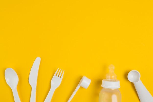 Vista superior de talheres de plástico e mamadeira para chá de bebê Foto gratuita
