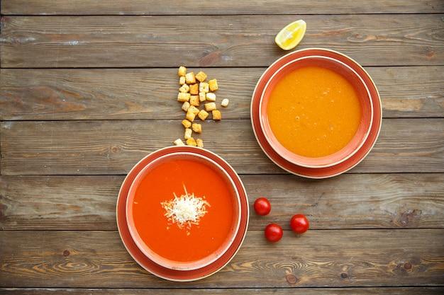 Vista superior de tigelas de sopa com sopas de tomate e lentilha em fundo de madeira Foto gratuita