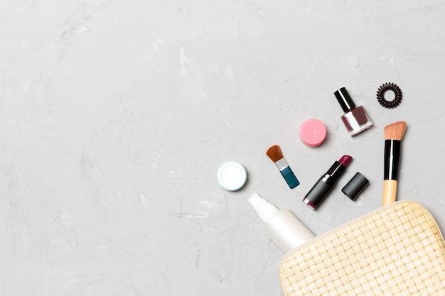 Vista superior de tornar-se produtos caídos de saco de cosméticos no cimento Foto Premium