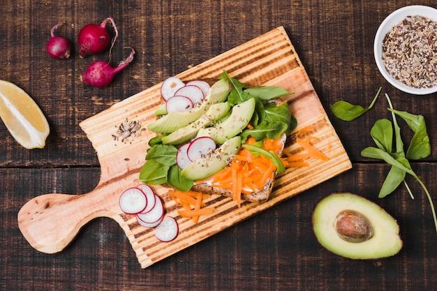 Vista superior de torrada com variedade de legumes Foto gratuita