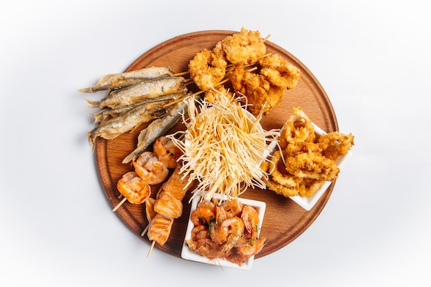 Vista superior de travessa isolada de cerveja de frutos do mar fritos com peixes e camarões Foto Premium