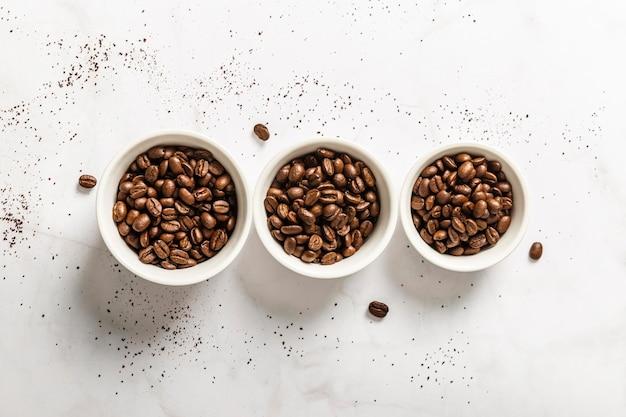 Vista superior de três xícaras com grãos de café torrados Foto gratuita