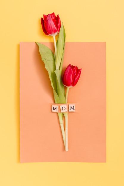 Vista superior, de, tulipa vermelha, flores, com, dia mãe, cartão cumprimento, sobre, experiência amarela Foto gratuita