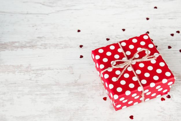 Vista superior de um boxe pontilhado vermelho do presente sobre a madeira branca, copyspace. Foto Premium