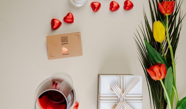 Vista superior de um buquê de tulipas com bombons de chocolate em forma de coração, embrulhados em papel alumínio vermelho, copo de vinho, cartão pequeno de papel pardo e uma caixa de presente na mesa branca Foto gratuita