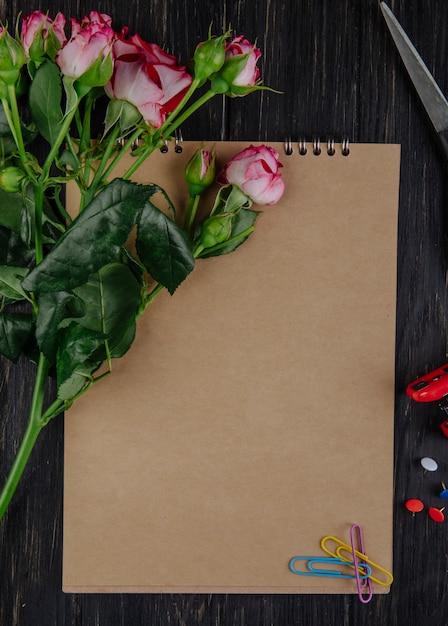 Vista superior de um caderno com rosas cor de rosa com botões deitado no fundo escuro de madeira Foto gratuita