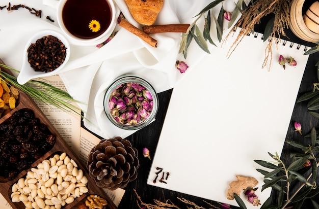 Vista superior de um caderno de desenho com botões de rosa chá em uma jarra de vidro, pinhas, nozes mistas e brunches de árvore com folhas e uma xícara de chá em madeira preta Foto gratuita