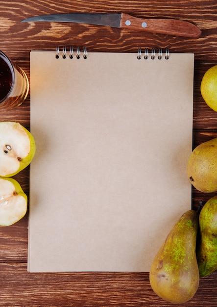 Vista superior de um caderno de desenho e peras frescas maduras com um copo de suco de pêra em fundo de madeira Foto gratuita