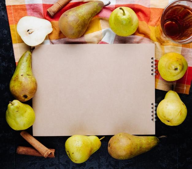 Vista superior de um caderno de desenho e peras maduras frescas, dispostas ao redor com um copo de suco de pêra em fundo preto Foto gratuita