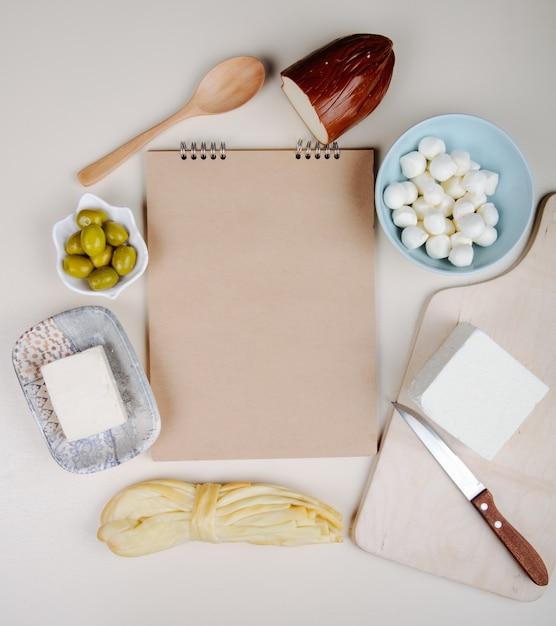Vista superior de um caderno de desenho e vários tipos de queijo mini mussarela em uma tigela azul, queijo feta, defumado e queijo com azeitonas em conserva na mesa branca Foto gratuita
