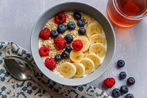 Vista superior de um café da manhã saudável com aveia em uma tigela, rodelas de banana, framboesa, mirtilo e uma xícara de chá na mesa cinza claro Foto Premium