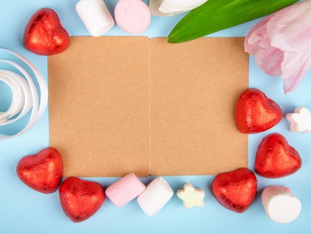 Vista superior de um cartão aberto de papel pardo com marshmallows espalhados e bombons de chocolate em forma de coração em folha vermelha com tulipas cor de rosa na mesa azul Foto gratuita