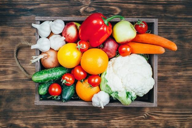 Vista superior de um conjunto de vegetais e frutas em uma caixa de madeira sobre uma mesa de madeira Foto Premium