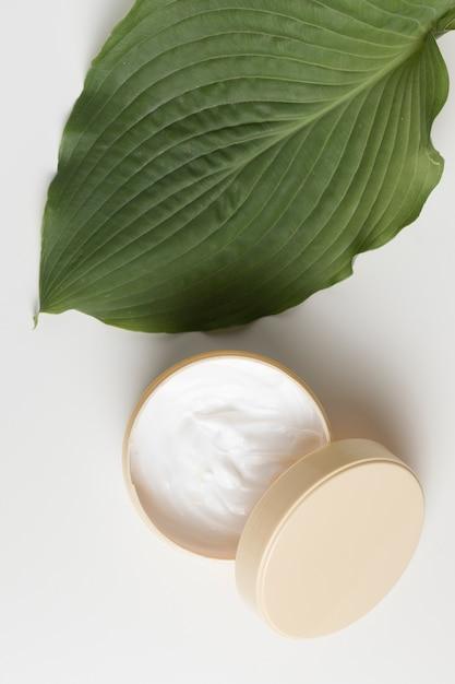 Vista superior de um creme e folha com fundo branco Foto gratuita